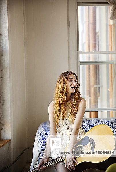 Woman with guitar looking away while sitting on bed at home
