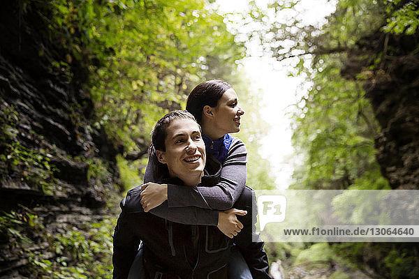 Mann nimmt seine Freundin beim Waldspaziergang huckepack