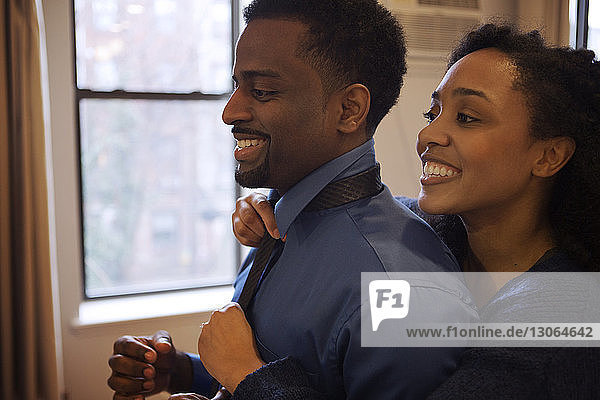 Woman assisting man in tying necktie at home
