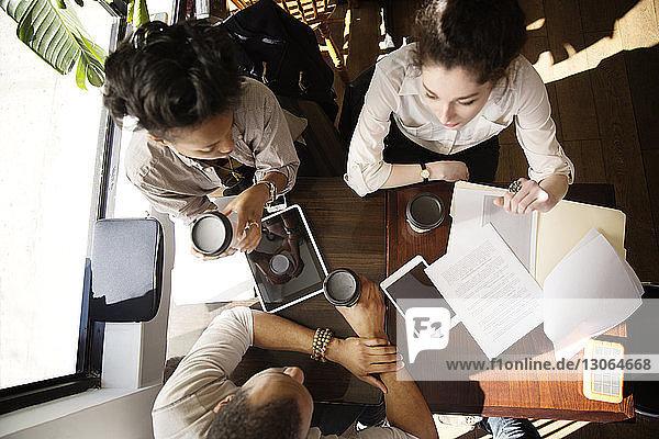 Draufsicht auf Kollegen  die diskutieren  während sie im Café sitzen