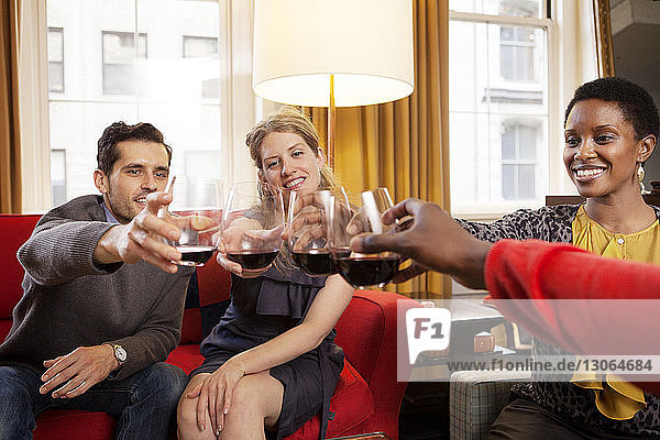 Happy friends toasting wineglasses while sitting on sofa