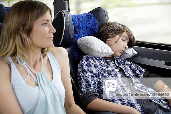 Mutter schaut weg  während der Sohn im Bus schläft
