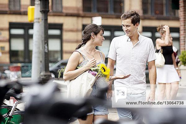 Freunde unterhalten sich beim Spaziergang auf einem Fußweg in der Stadt