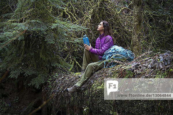 Frau hält Flasche und schaut auf  während sie im Wald auf einem umgefallenen Baumstamm sitzt