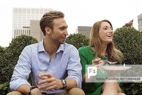 Couple looking away while sitting on building terrace
