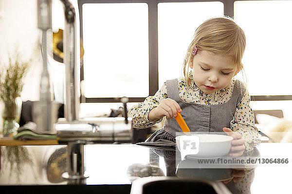 Mädchen betrachtet Schüssel  während sie zu Hause am Tisch sitzt