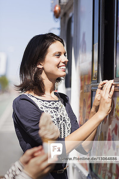 Smiling woman standing by ice cream truck