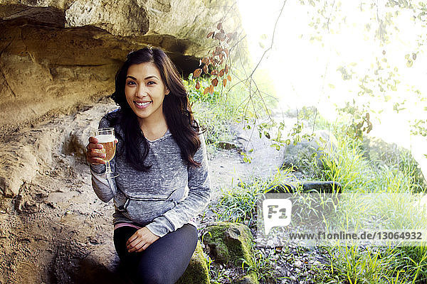 Portrait of woman holding glass while sitting on rock in forest