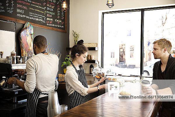 Frau benutzt Desktop-Computer  während sie dem Kunden einen Muffin serviert