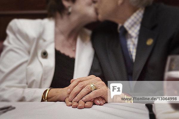 Mittelteil eines älteren Paares  das sich küsst  während es im Restaurant sitzt