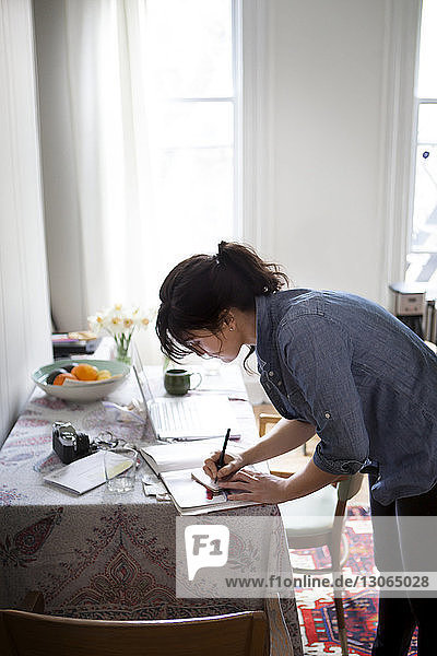 Side view of woman writing while standing by table at home