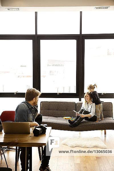 Frau sieht Mann an  während sie mit Tochter zu Hause auf dem Sofa sitzt