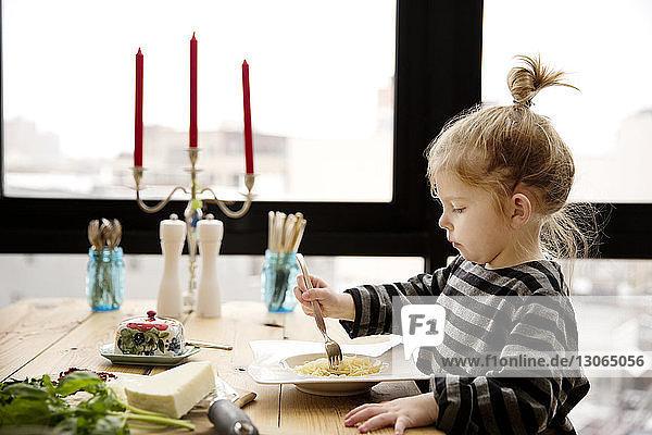 Mädchen isst zu Hause Nudeln bei Tisch