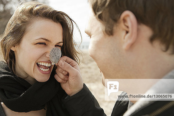 Man holding shell on woman nose while standing at beach