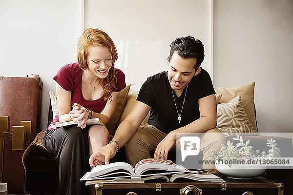 Paar liest Buch  während es zu Hause auf dem Sofa sitzt