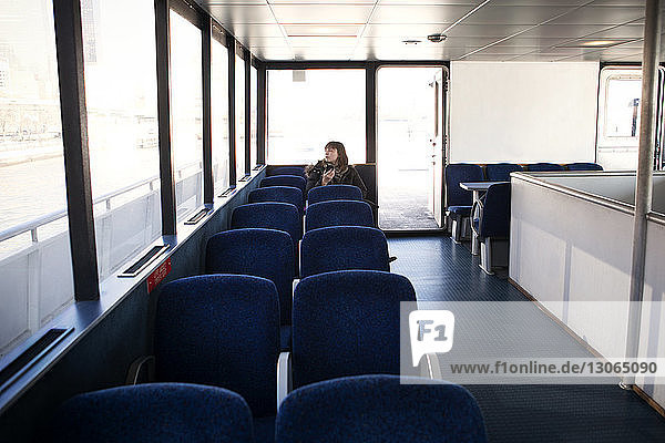 Woman looking away while sitting on seat in ferry