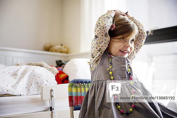 Glückliches Mädchen schaut weg  während es zu Hause auf einem Stuhl sitzt