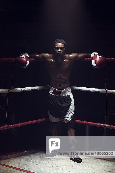 Portrait of male athlete leaning while standing in boxing ring