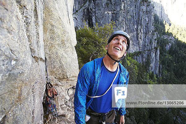 Glücklicher Mann schaut auf  während er an einer Felsformation gegen den Berg steht