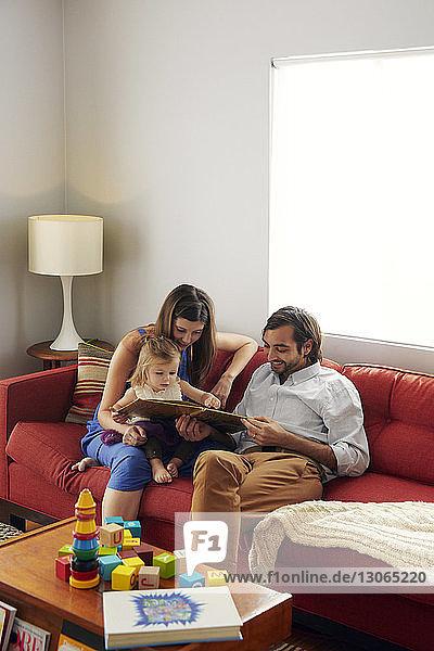 Vater und Mutter zeigen einem Mädchen ein Bilderbuch  während sie zu Hause auf dem Sofa sitzen