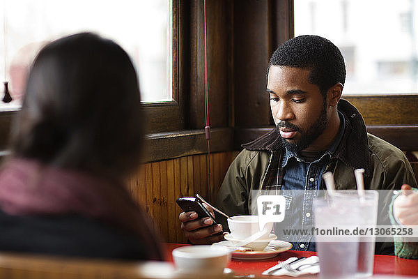 Man using smart phone while sitting with friends in restaurant