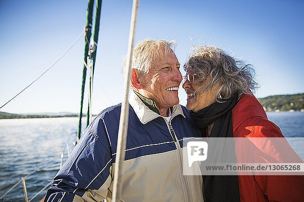 Fröhliches älteres Ehepaar auf einer Yacht auf See vor klarem Himmel