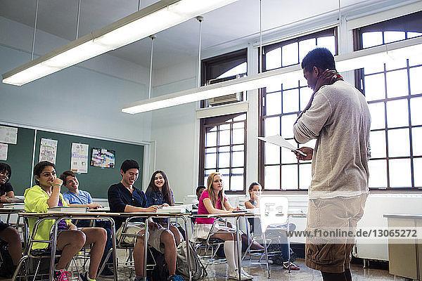 Schüler  die einen Teenager betrachten  der im Klassenzimmer Notizen liest