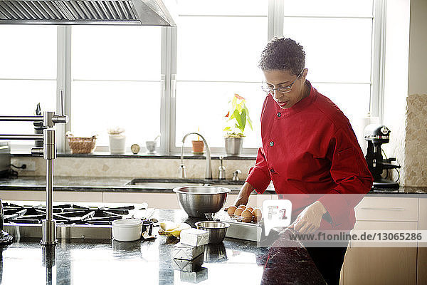 Woman using tablet computer on kitchen counter while preparing food