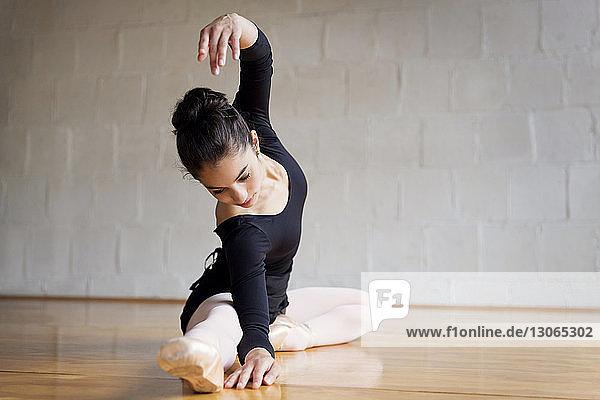 Frau tanzt  während sie im Ballettstudio auf dem Boden sitzt