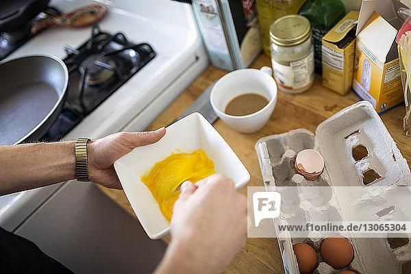 Beschnittenes Bild eines Mannes  der in der Küche Eier schlägt