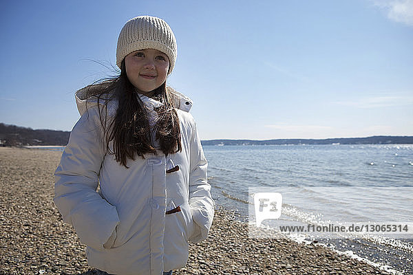 Cute girl standing at beach against sky