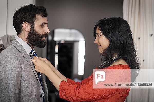 Lächelnde Frau passt Krawatte am Ehemann zu Hause an