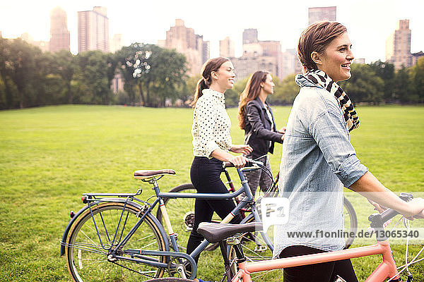 Frauen mit Fahrrädern gehen auf dem Feld im Park gegen die Stadt