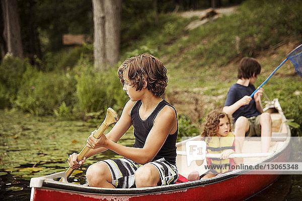 Kinder rudern im Kanu sitzend Kinder rudern im Kanu sitzend