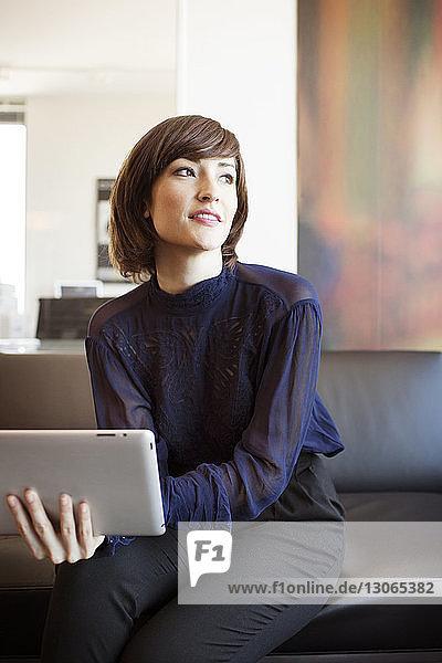 Frau mit Tablet-Computer schaut weg  während sie im Büro auf dem Sofa sitzt