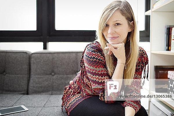 Porträt einer Frau  die zu Hause auf dem Sofa sitzt