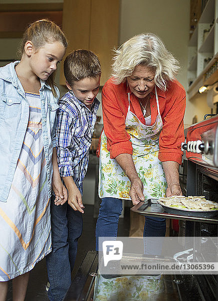 Family baking food in oven at home