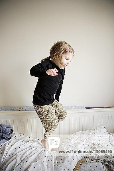 Verspieltes Mädchen  das zu Hause auf dem Bett hüpft