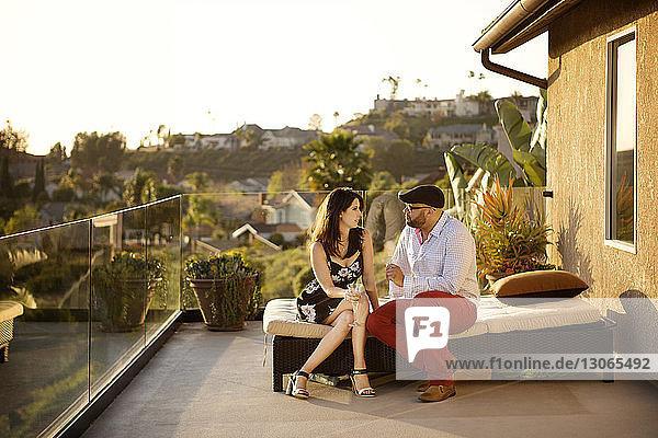 Freunde unterhalten sich  während sie auf einem Sitzplatz auf dem Balkon sitzen