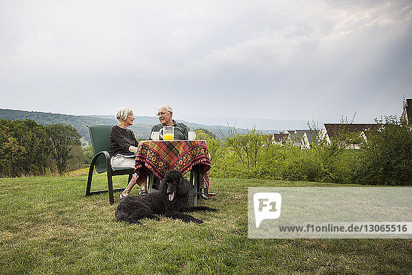 Senior couple at sitting breakfast table in lawn against sky