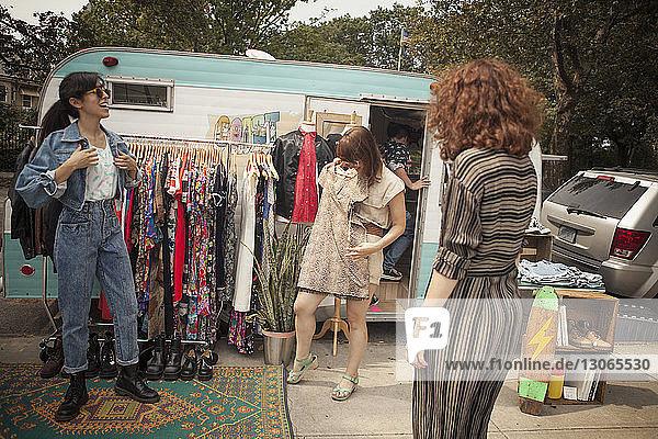 Eigentümer betrachtet Kunden bei der Auswahl der Kleidung  während er vor dem Wohnmobil steht