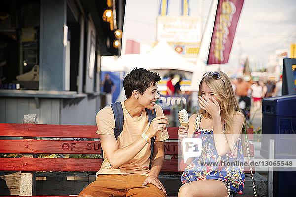 Glückliches Paar isst Eis  während es auf einer Bank im Vergnügungspark sitzt