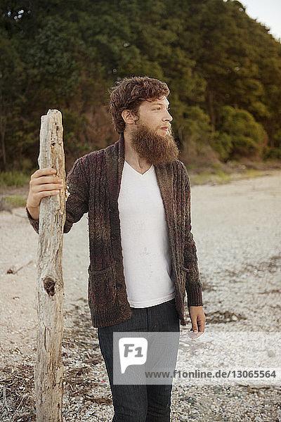 Mann schaut weg  während er auf Sand am Strand steht