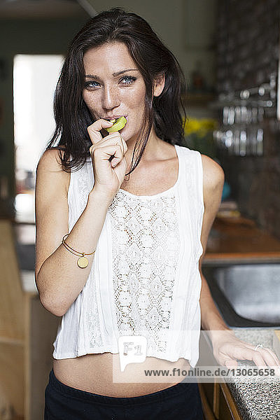 Portrait of woman eating kiwi while standing by kitchen counter at home
