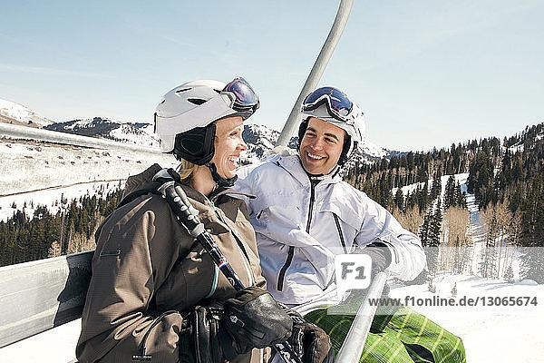 Glückliches Paar sitzt im Skilift vor klarem Himmel