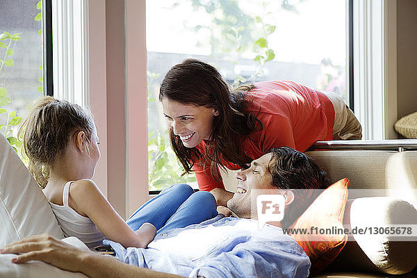 Parents looking at girl while sitting on sofa at home