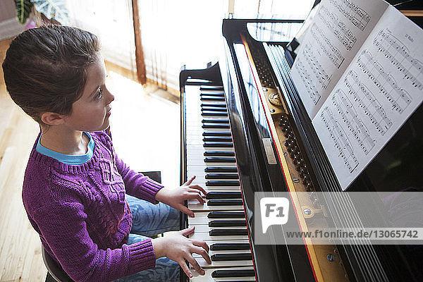 Girl practicing piano at home