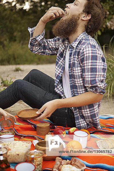 Freunde beim Frühstück auf einer Picknickdecke im Wald sitzend