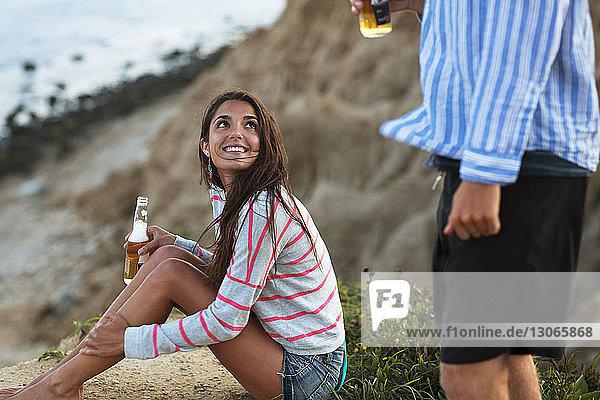 Frau mit Bierflasche schaut ihren Freund an  während sie auf dem Feld sitzt