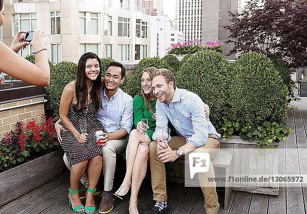 Frau fotografiert Freunde  die auf einem Tisch im Hof sitzen